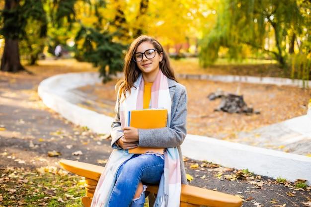 Junge hübsche frau, die ein buch liest und auf der bank im park sitzt. herbstzeit.