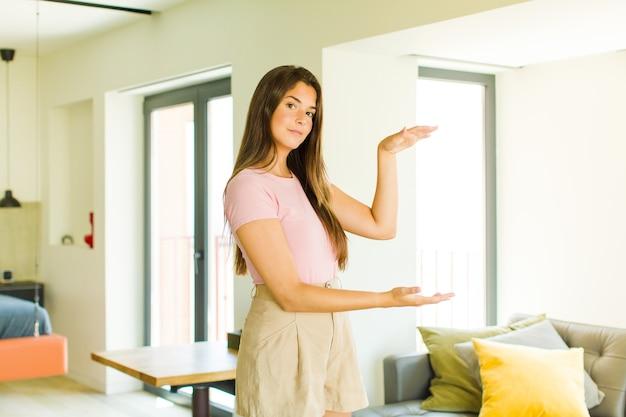 Junge hübsche frau, die ein objekt mit beiden händen auf seitenkopierraum hält, ein objekt zeigt, anbietet oder bewirbt
