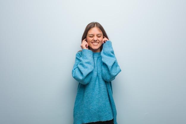 Junge hübsche frau, die eine blaue strickjacke bedeckt ohren mit den händen trägt