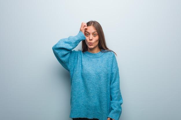 Junge hübsche frau, die eine blaue strickjacke gesorgt und überwältigt trägt