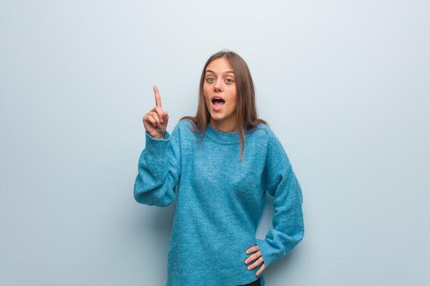 Junge hübsche frau, die eine blaue strickjacke hat eine idee, inspirationskonzept trägt