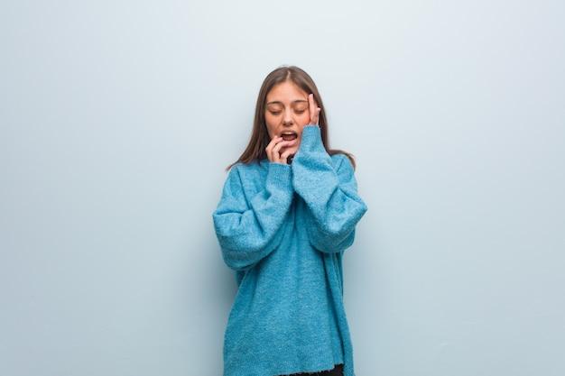 Junge hübsche frau, die eine blaue strickjacke hoffnungslos und traurig trägt