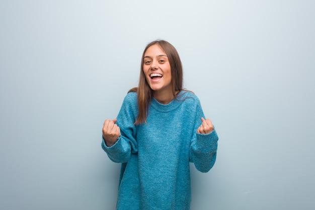 Junge hübsche frau, die eine blaue strickjacke überrascht und entsetzt trägt