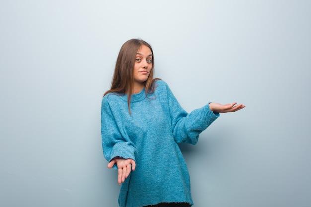 Junge hübsche frau, die eine blaue strickjacke verwirrt und zweifelhaft trägt
