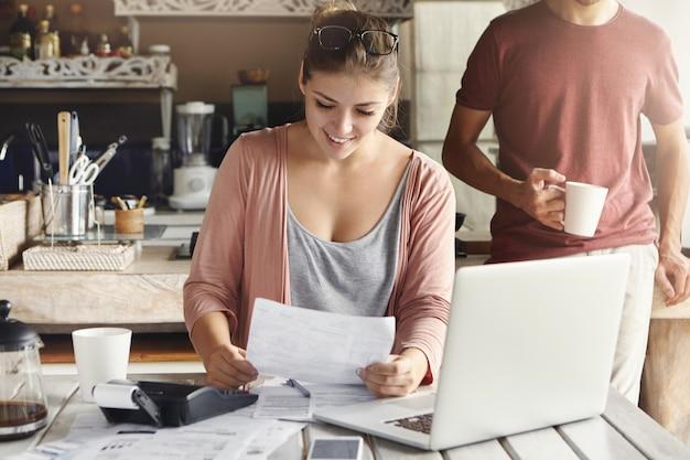 Junge hübsche frau, die eine brille auf ihrem kopf trägt, lächelt glücklich, während sie dokument liest, das sagt, dass bank ihren hypothekenantrag genehmigte
