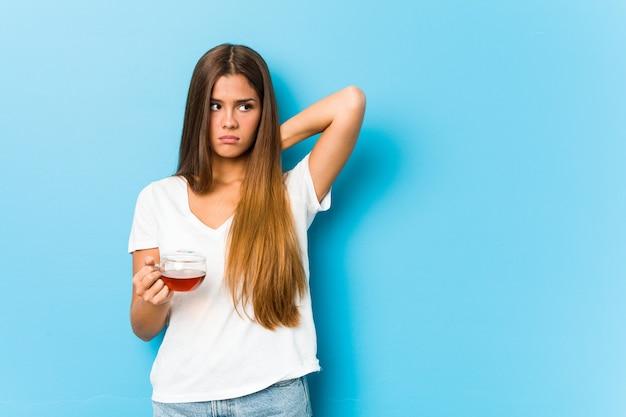 Junge hübsche frau, die eine teetasse hält, die hinterkopf berührt, denkt und eine wahl trifft.