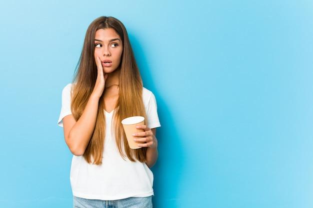 Junge hübsche frau, die einen kaffee zum mitnehmen hält, sagt eine geheime heiße bremsnachricht und schaut zur seite