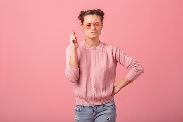 Junge hübsche frau, die einen wunsch macht, der finger im rosa pullover und in der sonnenbrille kreuzt, die auf rosa studiohintergrund lokalisiert werden