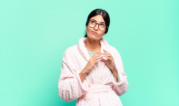 Junge hübsche frau, die entwirft und verschwört, verschlagene tricks und betrüger denkt, gerissen und verrät. pyjama-konzept