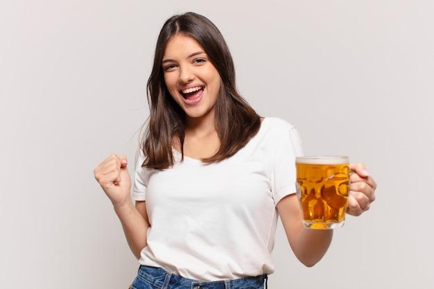 Junge hübsche frau, die erfolgreich einen sieg feiert und ein bier hält