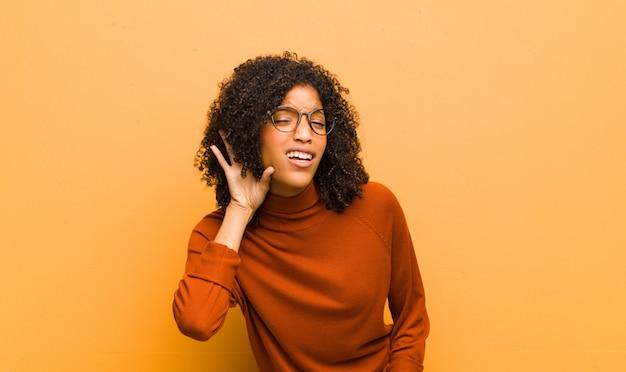 Junge hübsche frau, die ernst und neugierig aussieht, zuhört, versucht, ein geheimes gespräch oder klatsch zu hören, lauscht gegen orangefarbene wand