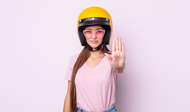 Junge hübsche frau, die ernsthafte offene handfläche zeigt, die stoppgeste macht. motorradfahrer und helm