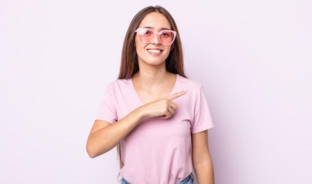 Junge hübsche frau, die fröhlich lächelt, sich glücklich fühlt und auf die seite zeigt. rosa sonnenbrillen-konzept