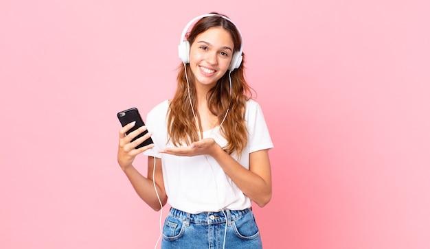 Junge hübsche frau, die fröhlich lächelt, sich glücklich fühlt und ein konzept mit kopfhörern und einem smartphone zeigt