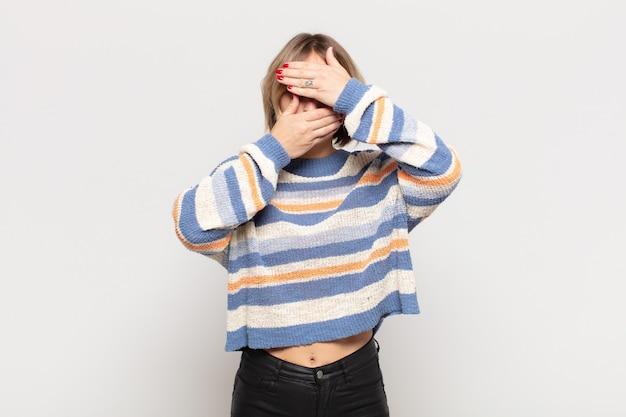 Junge hübsche frau, die gesicht mit beiden händen bedeckt, sagt nein zur kamera! bilder ablehnen oder fotos verbieten