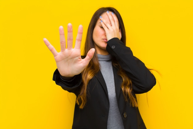 Junge hübsche frau, die gesicht mit hand bedeckt und andere hand vorne setzt, die fotos oder bilderjob oder geschäftskonzept ablehnt