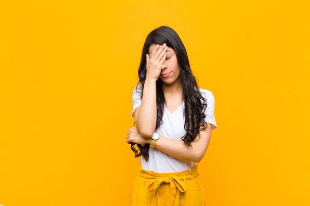 Junge hübsche frau, die gestresst, beschämt oder verärgert mit kopfschmerzen aussieht und gesicht mit hand gegen orange wand bedeckt