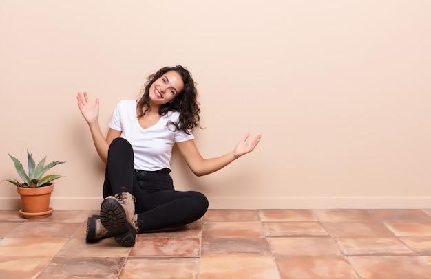 Junge hübsche frau, die glücklich, arrogant, stolz und selbstzufrieden aussieht und sich wie eine nummer eins fühlt, die einen terrassenboden sitzt