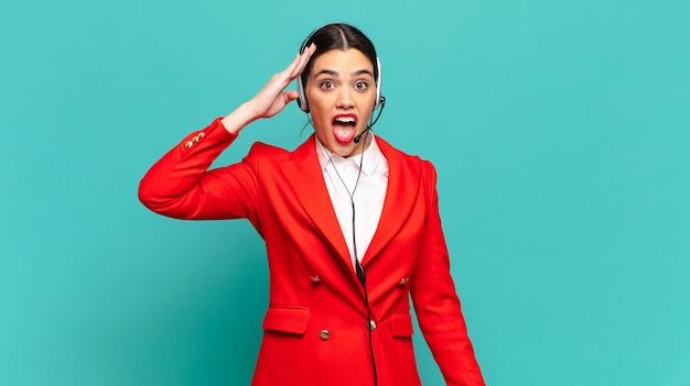 Junge hübsche frau, die glücklich, erstaunt und überrascht aussieht, lächelt und erstaunliche und unglaublich gute nachrichten erkennt. telemarketing-konzept
