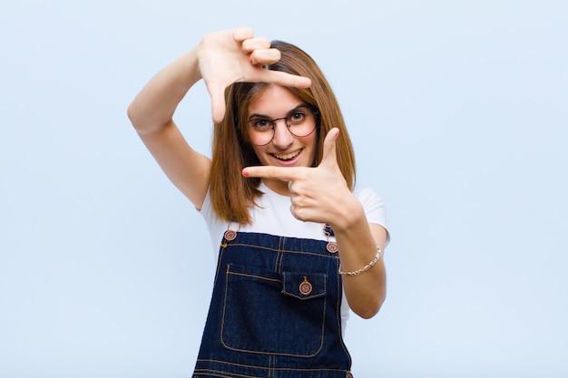 Junge hübsche frau, die glücklich, freundlich und positiv fühlt, lächelt und ein porträt oder fotorahmen mit händen gegen blauen hintergrund macht