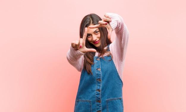 Junge hübsche frau, die glücklich, freundlich und positiv fühlt, lächelt und ein porträt oder fotorahmen mit händen gegen rosa wand macht.