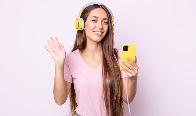 Junge hübsche frau, die glücklich lächelt, hand winkt, sie begrüßt und begrüßt. kopfhörer und smartphone