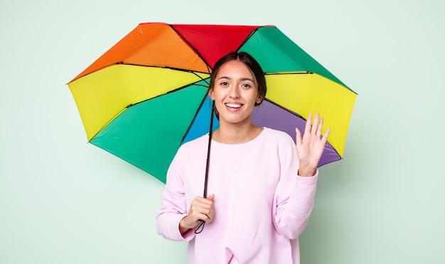 Junge hübsche frau, die glücklich lächelt, hand winkt, sie begrüßt und begrüßt. regenschirmkonzept