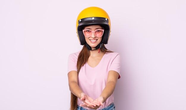 Junge hübsche frau, die glücklich mit freundlichem lächelt und ein konzept anbietet und zeigt. motorradfahrer und helm