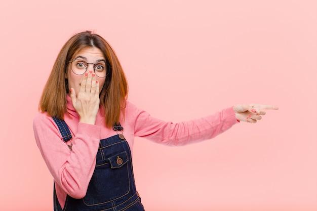 Junge hübsche frau, die glücklich, schockiert und überrascht fühlt, mund mit hand bedeckt und auf seitlichen kopierraum vor rosa hintergrund zeigt