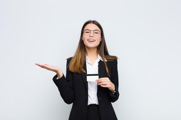Junge hübsche frau, die glücklich, überrascht und fröhlich fühlt, mit positiver einstellung lächelt und eine lösung oder idee mit einer kreditkarte verwirklicht