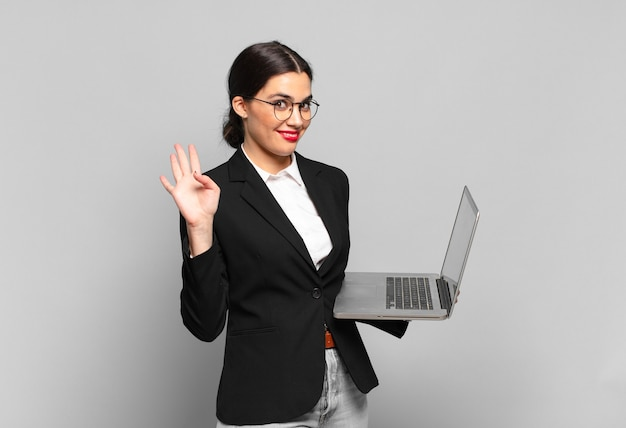 Junge hübsche frau, die glücklich und fröhlich lächelt, die hand winkt, sie begrüßt und begrüßt oder sich verabschiedet. laptop-konzept