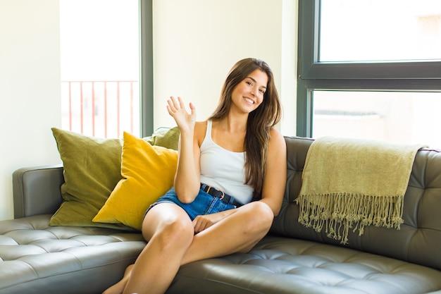 Junge hübsche frau, die glücklich und fröhlich lächelt, hand winkt, sie begrüßt und begrüßt oder sich verabschiedet