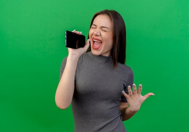 Junge hübsche frau, die hand in der luft hält, die mit geschlossenen augen singend unter verwendung des mobiltelefons als mikrofon lokalisiert auf grünem hintergrund mit kopienraum hält