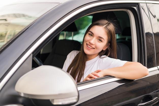 Junge hübsche frau, die ihr auto auf reisestraße fährt