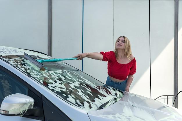Junge hübsche frau, die ihr auto in der selbstbedienungswaschanlage mit bürste in weißem schaum säubert