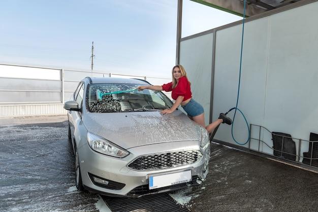Junge hübsche frau, die ihr auto in selbstbedienungs-autowaschanlage mit bürste in weißem schaum reinigt