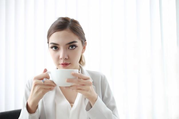 Junge hübsche frau, die im büro sitzt, trinken heiße kaffeetasse