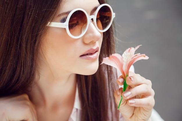 Junge hübsche frau, die im sonnigen sommertag mit kleiner schöner blume aufwirft