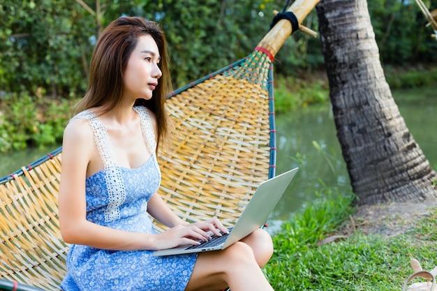 Junge hübsche frau, die in der bambushängematte unter verwendung des laptops sitzt