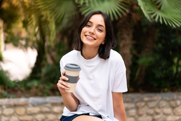 Junge hübsche frau, die kaffee hält, um im freien wegzunehmen