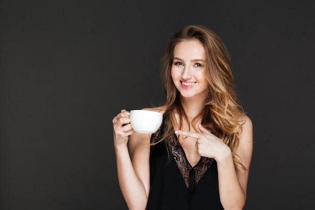 Junge hübsche frau, die kaffee trinkt und zeigt