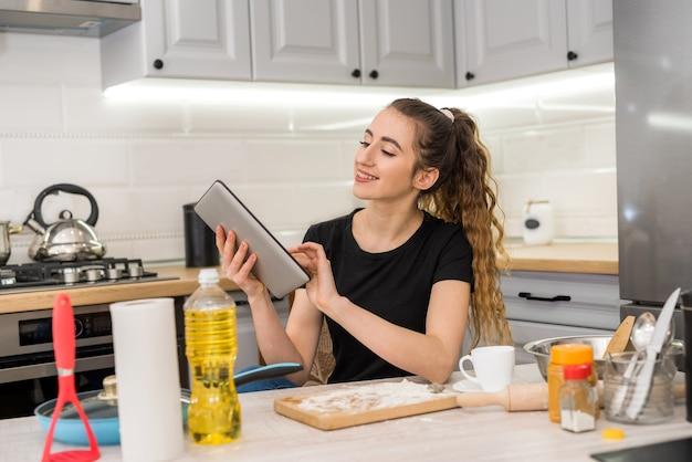 Junge hübsche frau, die kekse zu hause mit hilfe digitaler tablette vorbereitet