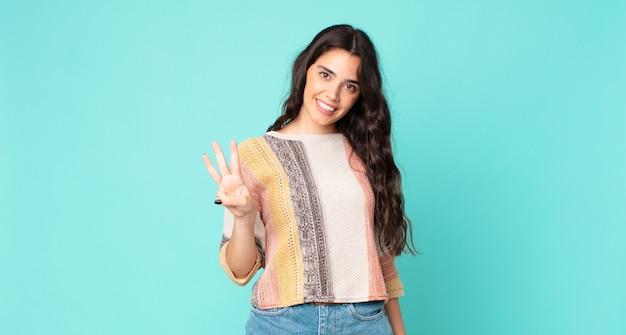Junge hübsche frau, die lächelt und freundlich aussieht, die nummer drei oder die dritte mit der hand nach vorne zeigt, herunterzählt