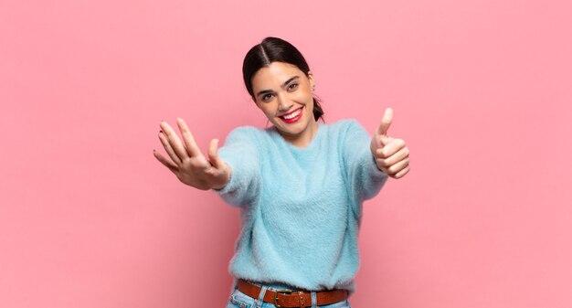 Junge hübsche frau, die lächelt und freundlich aussieht, die nummer sechs oder sechs mit der hand nach vorne zeigt und herunterzählt