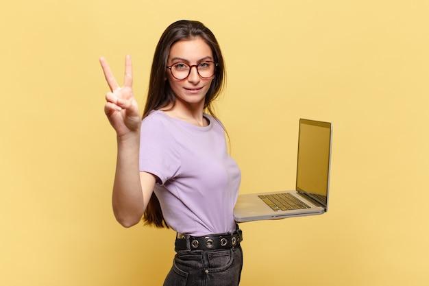 Junge hübsche frau, die lächelt und freundlich aussieht, die nummer zwei oder die zweite mit der hand nach vorne zeigt, herunterzählen. laptop-konzept
