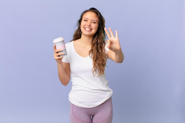 Junge hübsche frau, die lächelt und freundlich aussieht, nummer drei zeigt und einen kaffee hält