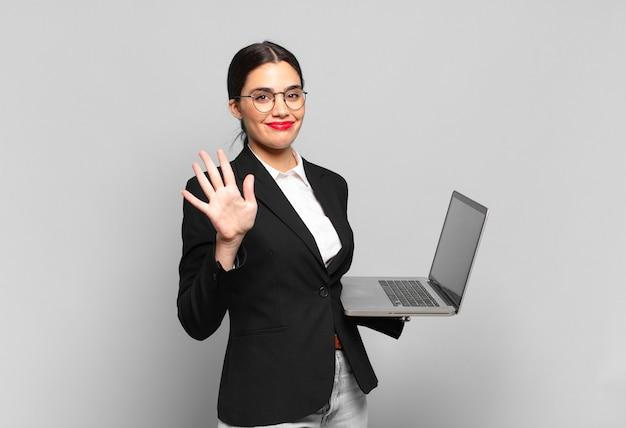 Junge hübsche frau, die lächelt und freundlich aussieht, nummer fünf oder fünf mit der hand nach vorne zeigend, rückwärts zählend. laptop-konzept