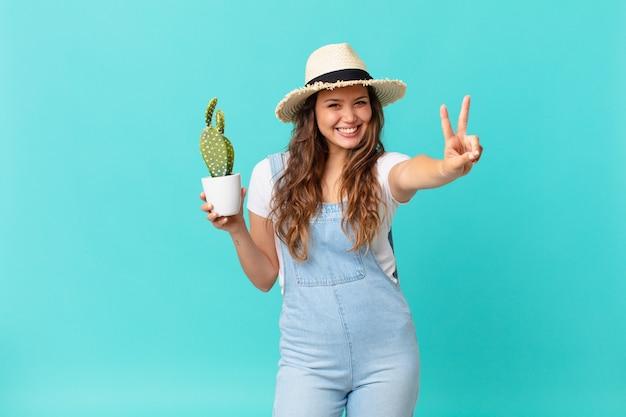 Junge hübsche frau, die lächelt und glücklich aussieht, sieg oder frieden gestikuliert und einen kaktus hält