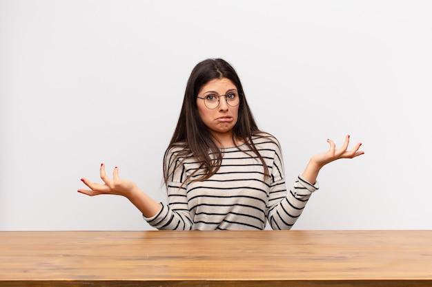 Junge hübsche frau, die mit einem dummen, verrückten, verwirrten, verwirrten ausdruck die achseln zuckt und sich genervt und ahnungslos an einem tisch sitzt