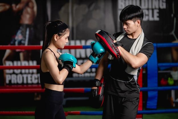 Junge hübsche frau, die mit einem gutaussehenden trainer im box- und selbstverteidigungskurs auf dem boxring im fitnessstudio trainiert, weibliche und männliche kampfhandlungen,